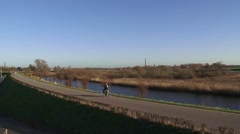 Cyclist across ancient  dike, river IJssel, The Netherlands Stock Footage