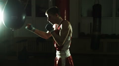 Silhouette of Young boxer hitting punching bag in gym Stock Footage