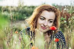 Beautiful caucasian woman posing with poppy flowers field, summer time Stock Photos