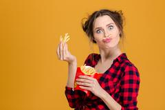 Funny pretty young woman making fake moustache with fries Stock Photos