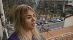 Pretty blonde girl smoking a cigarette, relaxing, looking at the view on terace Stock Footage