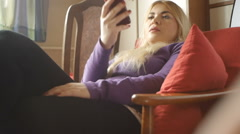Cute blonde girl, relaxin home, texting cell phone Stock Footage