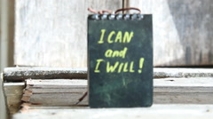 I can and I will, yellow lettering on a black plate. - stock footage