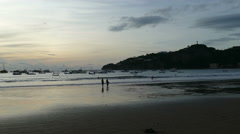 People walking at sunset on the beach of San Juan del Sur Stock Footage