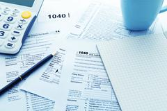 Income tax return form with calculator and pen - stock photo