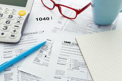 Income tax return form with calculator and notebook and pen - stock photo