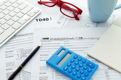 Income tax return form with computer keyboard calculator and notebook Stock Photos