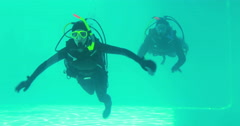 Couple in scuba gear swimming Stock Footage