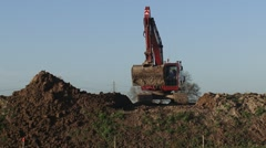 Stock Video Footage of crawler excavator rides across clay dike and starts digging - on camera