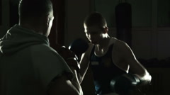 The boxing coach trains the young boxer Stock Footage