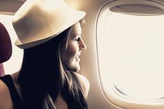 Young woman is looking through a window in the aircraft - stock photo