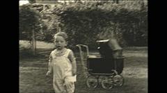 Vintage 16mm film, 1935, people, children playing, boy pushing pram Stock Footage