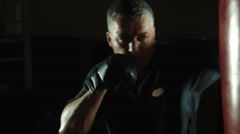Workout of Boxer with sweaty face hitting red punching bag Stock Footage