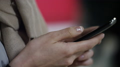 Close up of young asian woman using her cell phone in a public place - stock footage