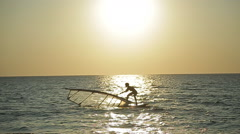 Surfer floating on the sea at sunset Stock Footage