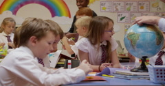 Teacher showing a globe to children in classroom Stock Footage