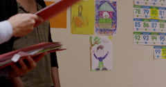 Teacher distributing books to children - stock footage