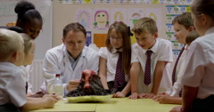 Teacher interacting with children while working on a science project Stock Footage