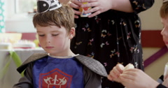 Two boys dressed in fancy costumes having sandwiches during a birthday party Stock Footage