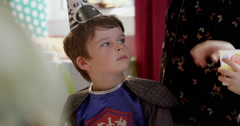 Boy dressed in fancy costume looking around during a birthday party in classroom Stock Footage