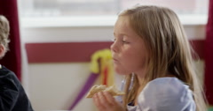 Girl having a sandwich during a birthday party in classroom - stock footage