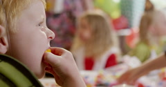 Boy having a slice of lemon during a birthday party in classroom Stock Footage