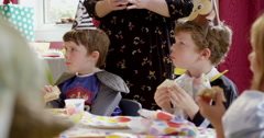 Children dressed in fancy costumes having sandwiches during a birthday party - stock footage
