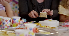Teacher distributing pieces of birthday cake to children - stock footage