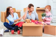 Stock Photo of The happy family  at repair and relocation