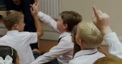 Students raising hands and interacting in classroom - stock footage