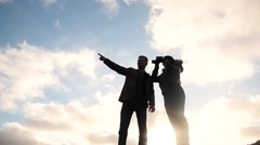 Man and woman against sun with binocular sky background Stock Footage