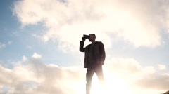 Man with binoculars against sun view slow motion Stock Footage