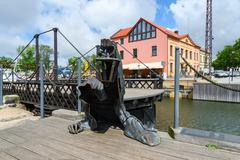 "Sculpture ""Black Ghost"" near wrought swing bridge, Klaipeda, Lithuania Stock Photos"