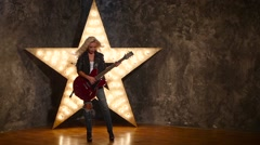 Sexy girl with electric guitar in leather, shining star in the background, slow Stock Footage