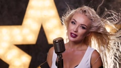 Sexy blonde woman Singing with Retro Microphone, shining star in the background Stock Footage