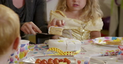 Teacher distributing pieces of birthday cake to children Stock Footage