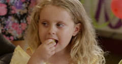 Girl having snacks during a birthday party Stock Footage