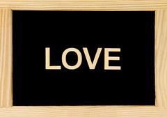 Wooden frame vintage chalkboard with word LOVE created of wood letters Stock Photos