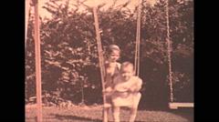 Vintage 16mm film, 1935, people, children on swing Stock Footage