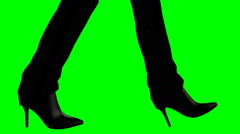High heeled black boots walking on a green screen Stock Footage