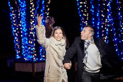 Happy young couple running in the evening park with illumination Stock Photos