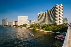Tall modern buildings along the Chao Phraya River, in Bangkok, Thailand. - stock photo
