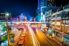 Long exposure of traffic and modern buildings on Ratchadamri Road at night, a - stock photo