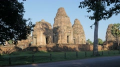 Woman on bicycle passing Pre Rup temple at Angkor complex,Siem Reap,Cambodia Stock Footage