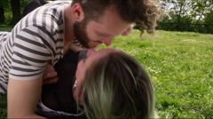 Romantic young couple lying on lawn and kissing Stock Footage