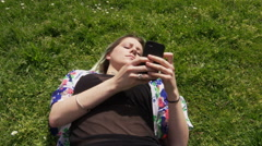 Stock Video Footage of Beautiful young woman lying on lawn and listening to music