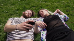 Stock Video Footage of Romantic young couple lying on lawn and listening to music