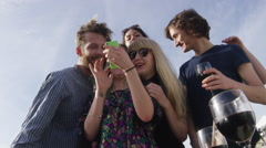 Friends looking and reacting to photos on mobile phone Stock Footage