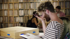 Young couple checking gramophone record in music store Stock Footage