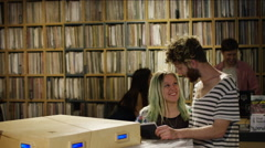 Young couple selecting gramophone records in music store - stock footage